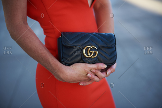 March 09, 2018- Melbourne, Australia: Young woman wearing red body con dress, holding Gucci mini bag purse