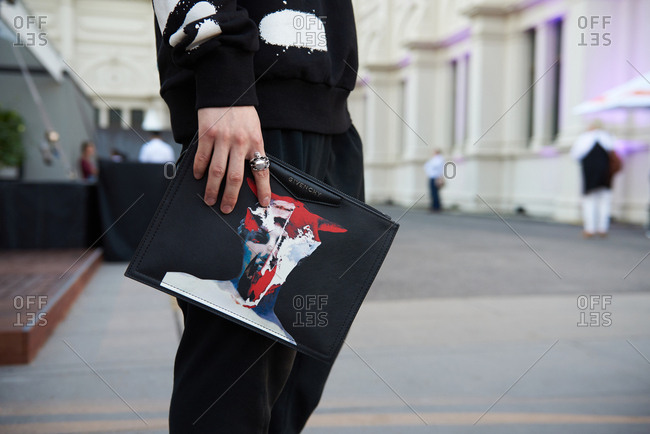 March 09, 2018- Melbourne, Australia: Male fashion event guest holding and Givenchy leather purse, low angle