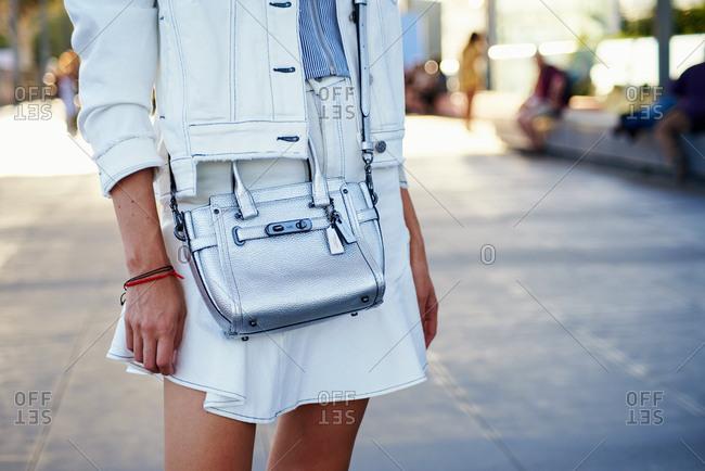 March 09, 2018- Melbourne, Australia: Fashion show guest wearing white denim summer look with Coach metallic crossbody bag