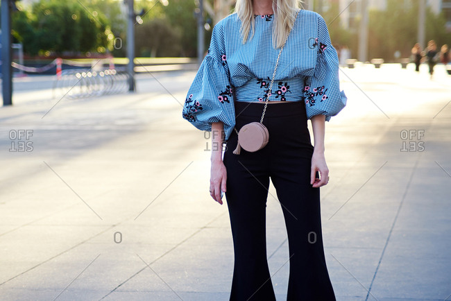 March 09, 2018- Melbourne, Australia: Fashion show guest wearing plaid top and circular crossbody bag in evening sunset light