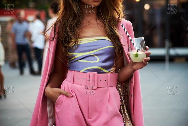 March 09, 2018- Melbourne, Australia: Fashion show guest wearing blush pink suit with high waisted belt, holding cocktail in evening light