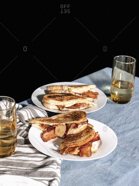 Two grilled bacon, apple, and brie cheese sandwiches on white plates on a table with water glasses.