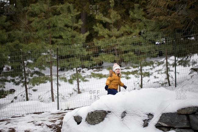 Little boy walking up snowy hill by forest