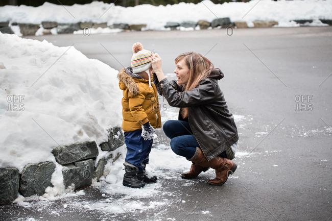 Mother adjusting little boy's hat in winter