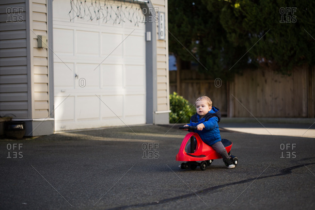 Toddler riding on red ride-on toy