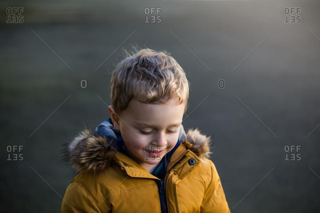 Portrait of a little blonde boy outside wearing yellow jacket looking down