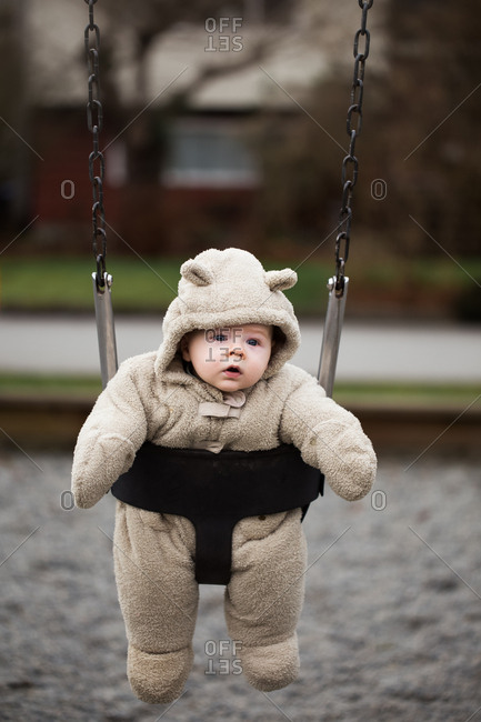 Baby in thick snowsuit in a swing