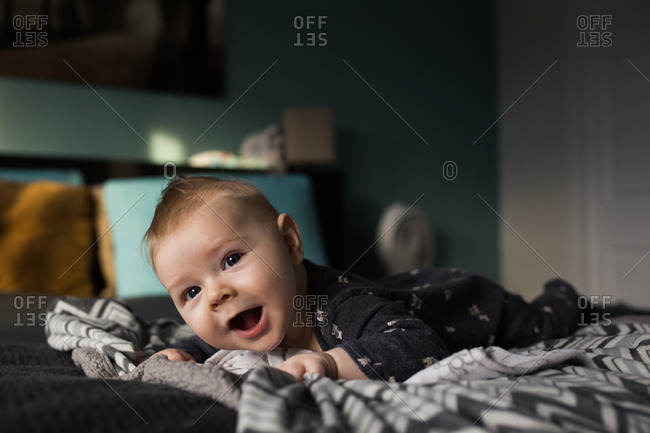 Happy baby doing tummy time on bed