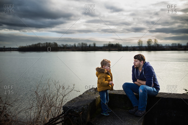 Father and son together by river