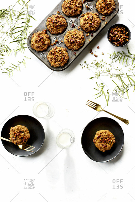 Pecan crumb cake muffins served beside pan with milk