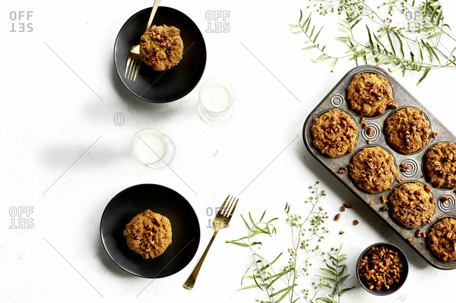 Pecan crumb cake muffins served with milk beside pan