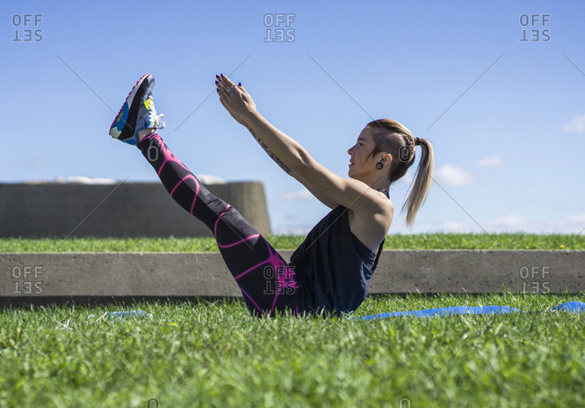 Young athletic woman doing yoga and using her flexibility during summer day