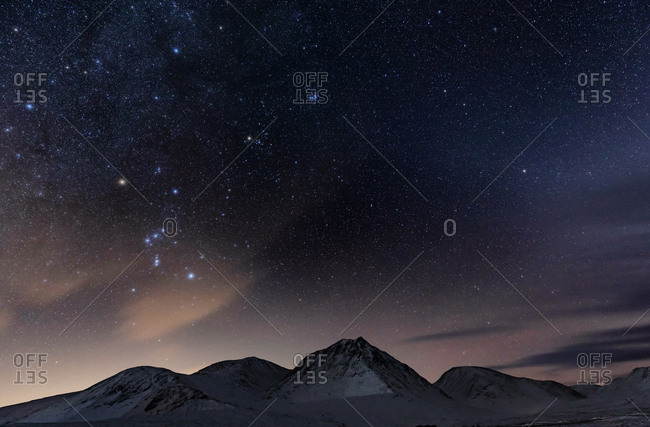 A snow covered mountain landscape and star filled sky in the Scottish highlands.