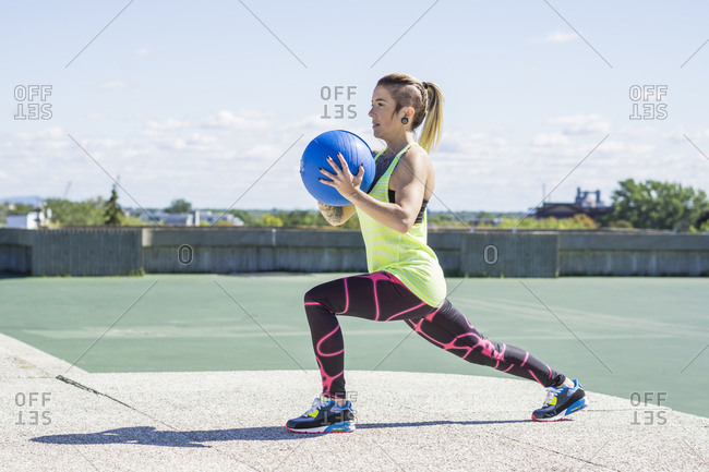 Female athlete working out with medicine ball on summer day in concrete public park