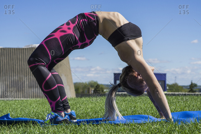 Young female athlete doing chakrasana yoga pose outside during summer