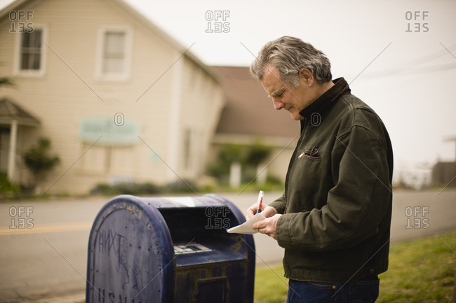 Man writing on letter next to post box
