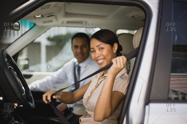 Man and woman sitting in car smiling at the camera