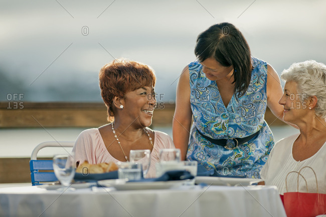 Two mature female friends out to lunch share a laugh with an acquaintance who has come to say hello.