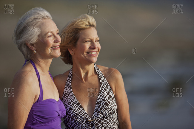 Smiling mature women standing on a beach.
