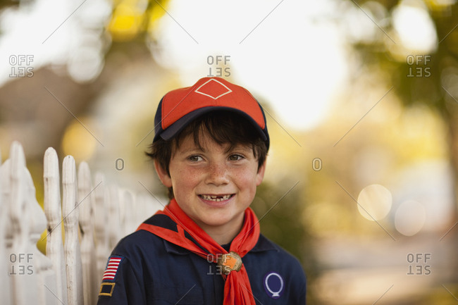 Boy Scout standing on a suburban street.