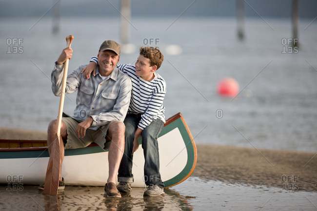 Father and son sitting in canoe at water's edge.
