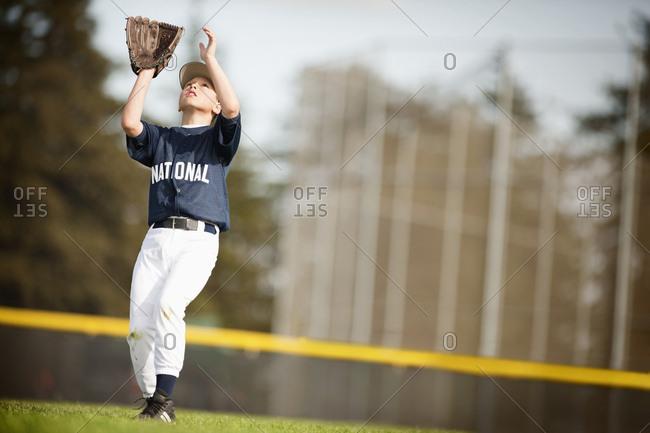 Pre-Adolescent boy catches a baseball.