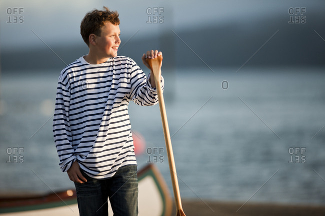 Boy holding oar at water's edge.