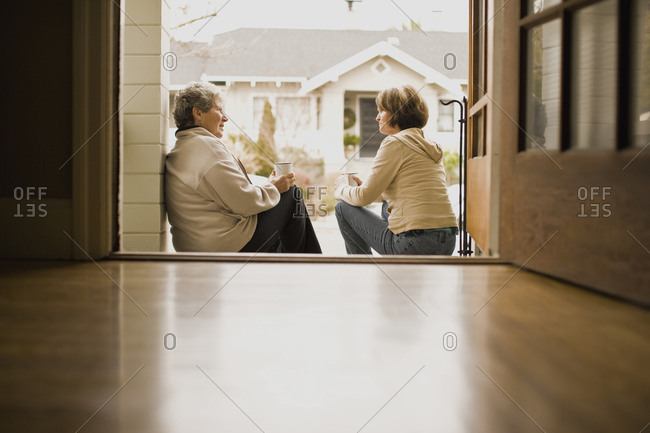 A mother and daughter catching up over coffee on the front stoop.