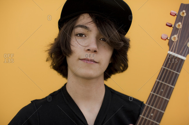 Portrait of a teenage boy wearing a hat and posing with his guitar.