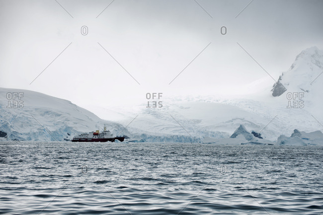 Ship passing through freezing waters and icy coastline.