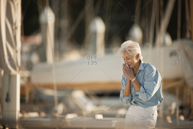 Senior woman smiles while standing at a marina.
