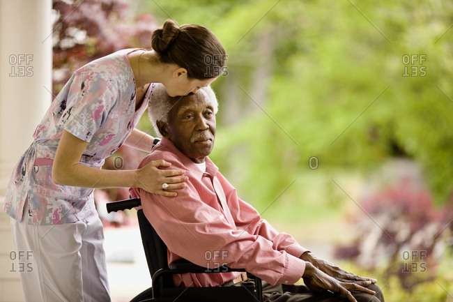 Nurse puts supportive hands on a senior man's shoulders and leans forward to kiss his forehead as he sits in a wheelchair on a porch.