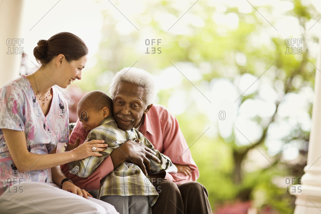 Nurse looks on happily as a senior man hugs a boy and she puts a supportive hand on the boy's arm.