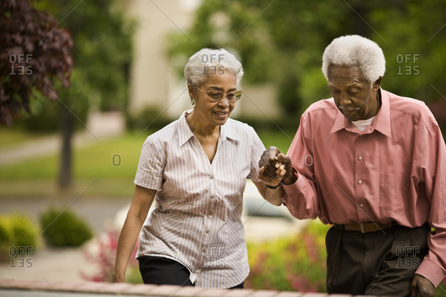 Senior couple hold hands as they walk up steps in a garden.