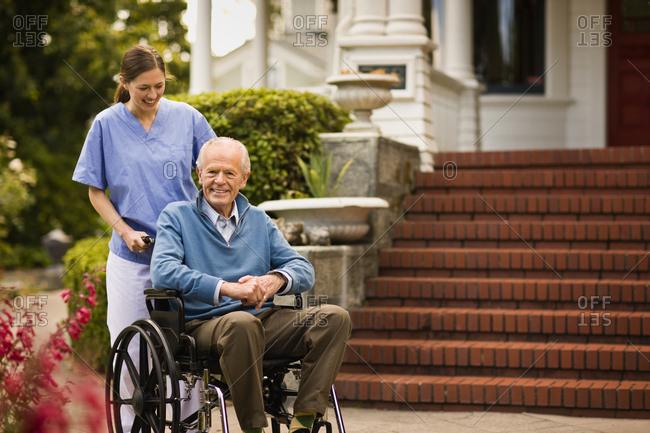 Young nurse pushes senior man in wheel chair.