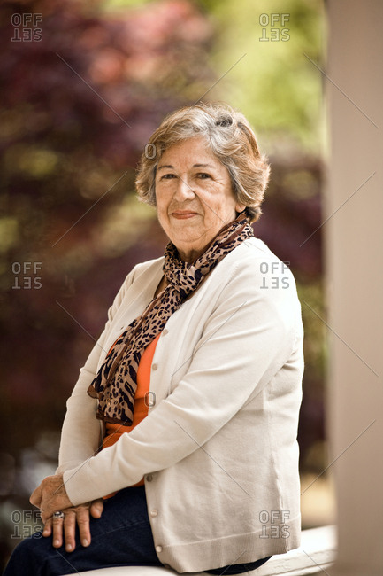 Senior woman smiles with her hands folded across her lap.