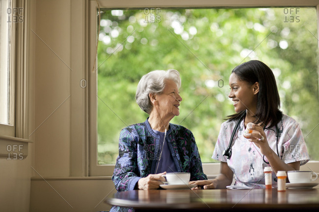 Female nurse explaining how to take medication to a senior patient.