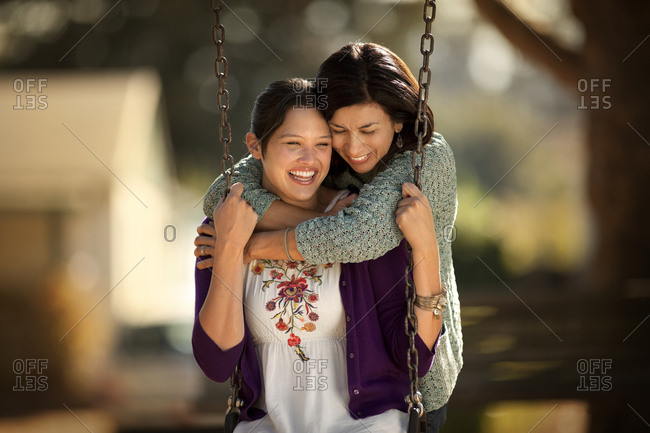 Happy teenage girl bonding with her mother at a park.