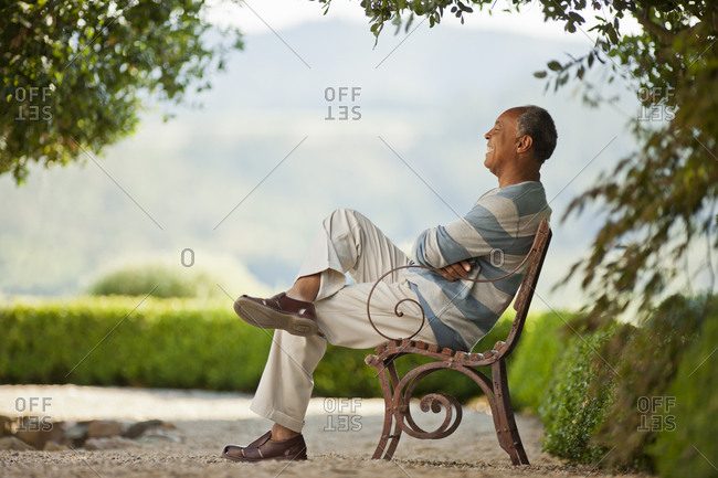 Smiling mature man sitting on a park bench.