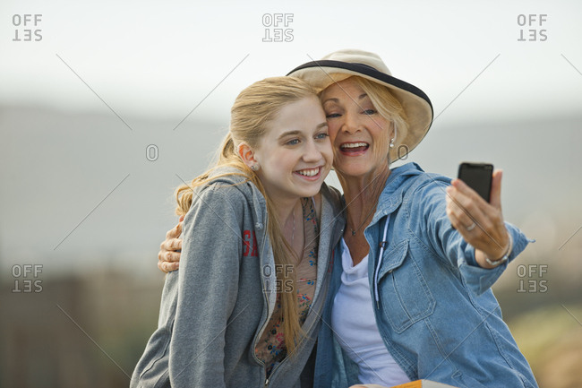 Smiling senior woman and granddaughter taking photos on a smart phone.