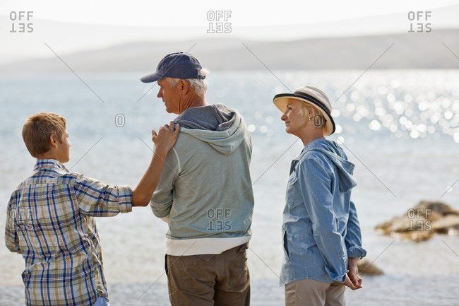 Teenage boy standing on a beach with his grandparents.
