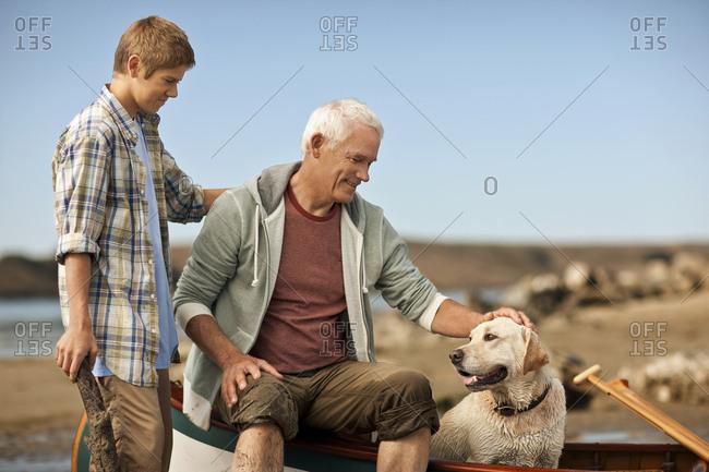 Happy senior man and grandson petting a dog.