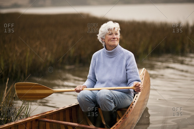 Mature woman smiles and looks away as she holds an oar ready to row and sits in the aft of a wooden canoe on a lake.