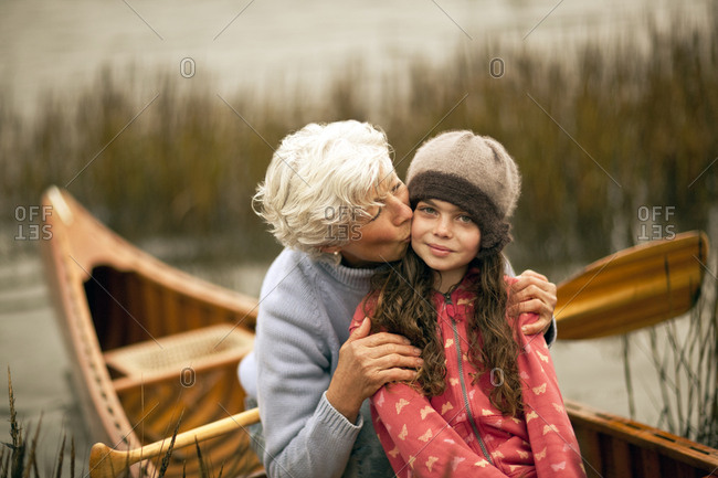Portrait of grandmother kissing her granddaughter on the cheek.