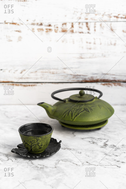Tea pot with cup with warm green tea in white background