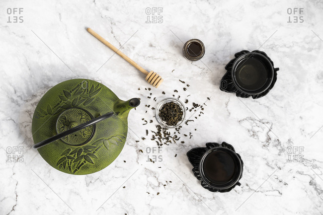 Teapot with cups with green tea and honey