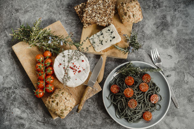 Arrangement of healthy Mediterranean food with pasta, bread, tomatoes, cheese and spices