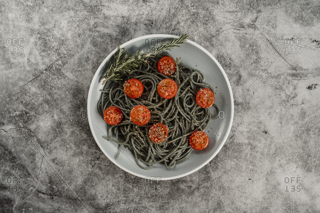 Dish of healthy Mediterranean food with spaghetti with tomatoes oregano and rosemary