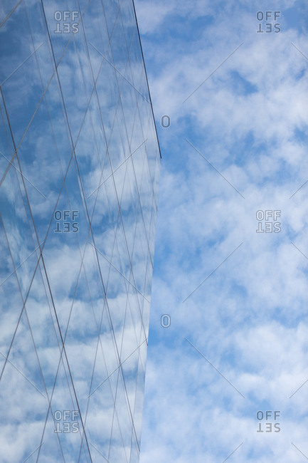 Bright clouds sky reflected on glass walled building