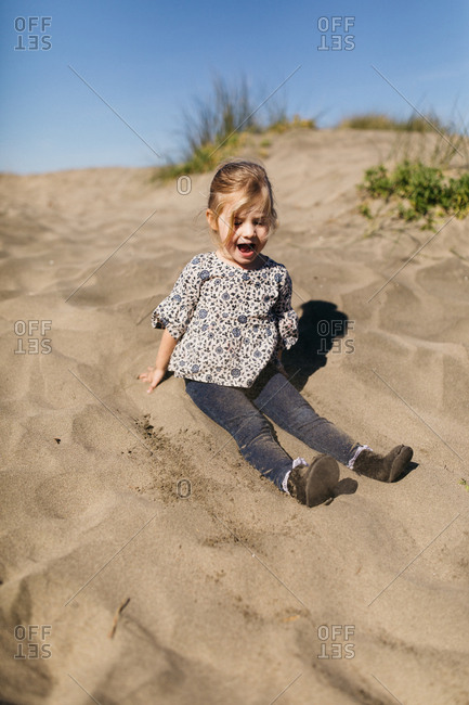 Little blonde girl playing on a sand dune